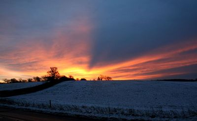 SUNSET OVER SNOWY FIELD